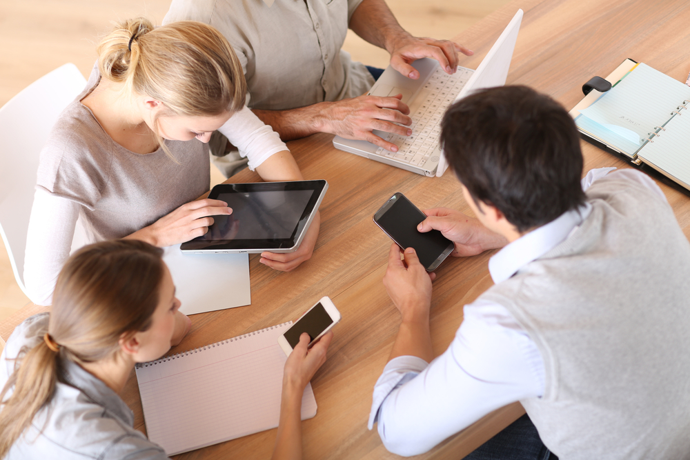Group of business people using electronic devices at work